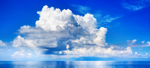 Zelfklevend Fotobehang Donkerblauw White cumulus clouds in blue sky over sea landscape, big cloud above ocean water panorama, horizon, beautiful tropical sunny summer day seascape panoramic view, cloudy weather, cloudscape, copy space
