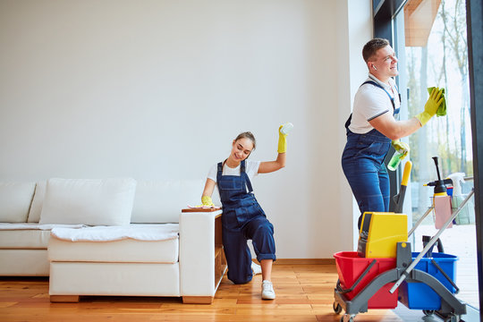 Man cleaning panoramic window and girl polishing sofa. Teamwork of cleaning company.