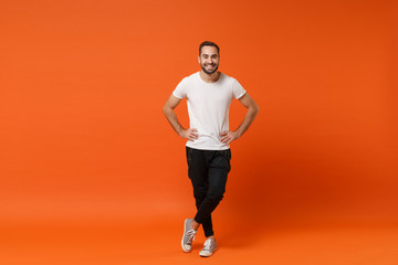 Smiling young man in casual white t-shirt posing isolated on orange wall background studio portrait. People sincere emotions lifestyle concept. Mock up copy space. Standing with arms akimbo on waist. Wall mural