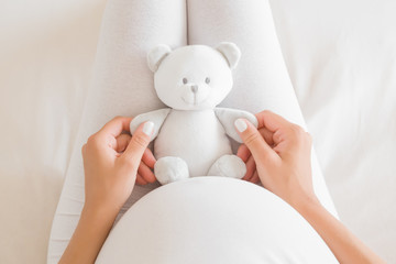Woman hands holding little smiling white teddy bear on lap for future baby. Homely atmosphere. Emotional loving moment in pregnancy time - 35 weeks. Baby expectation. Top down view. Point of view.