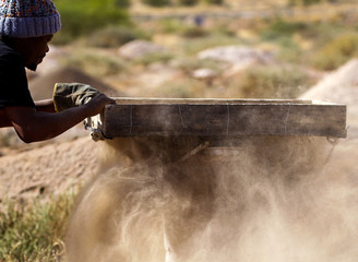 A member of the Batho Pele cooperative of artisanal miners sifts through sand and rocks searching for diamonds in Kimberley