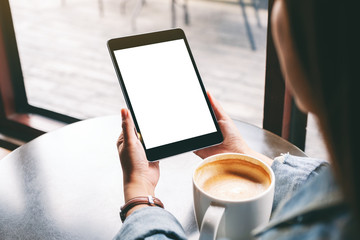 Mockup image of a woman holding black tablet with white blank screen and coffee cup on the table