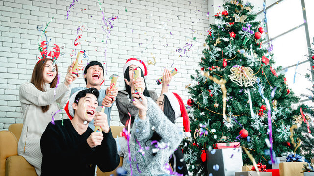 Asian people party celebrate christmas and new year eve in house and christmas tree decorate with confetti paper shoot
