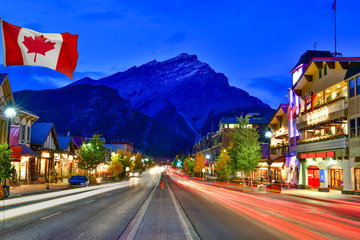 Canadian flag with Banff Avenue at twilight time, Alberta, Canada
