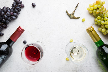 Glasses of white and red wine with ripe grapes on stone background, top view