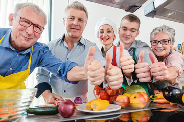 Trainees and their nutritionist in a training kitchen showing thumbs