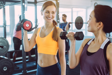 Two women doing fitness training together in the gym