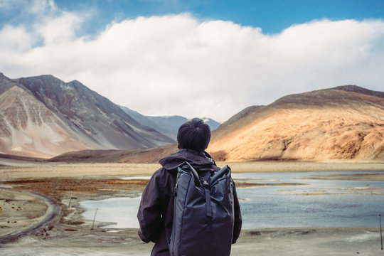 Young wanderlust traveler with backpack against Pangong Lake in Leh, Ladakh, India. Travel trip and Tourism concept background.