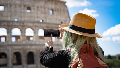 Back view of young woman  with hat take a picture by smartphone at Colosseum in Rome landmark which Rome Colosseum is one of the best known monuments of Rome and Italy