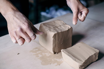 Female potter hands working with clay in workshop. White desk on background Fototapete