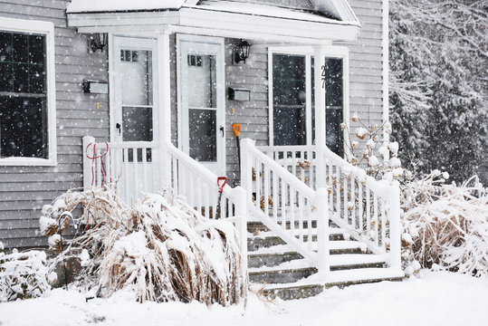 a small cozy house covered with snow during the snowfall. The atmosphere of winter comfort and weather.