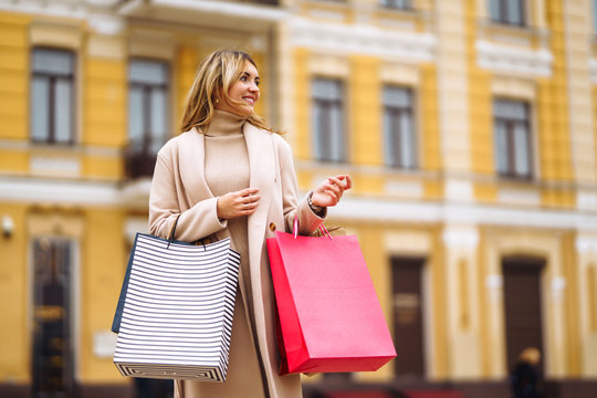 Young woman holding shoopping bags in the city street. Blond girl in a light coat smiling and hold in her hands colorful shooping bags. Consumerism, purchases, shopping, sales, lifestyle concept.