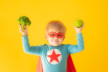 Foto op Plexiglas Keuken Superhero child holding broccoli and apple