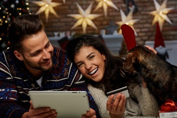 Christmas couple shopping on tablet at home