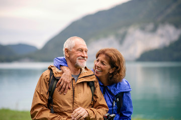Senior pensioner couple hiking by lake in nature, resting. Wall mural