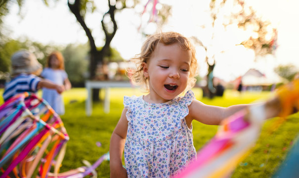 A front view of small girl on birthday party outdoors in garden in summer.