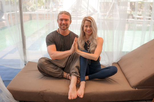 holiday yoga retreat portrait of young happy and beautiful hipster couple sitting in lotus position together enjoying zen lifestyle smiling cheerful and relaxed