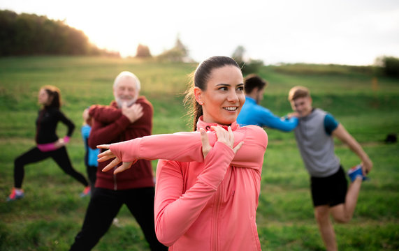 Large group of fit and active people stretching after doing exercise in nature.