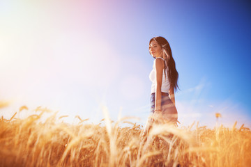 Happy woman enjoy the life in the field. Nature beauty, blue sky,white clouds and field with golden wheat. Outdoor lifestyle. Freedom concept. Woman walk in summer field Fotoväggar