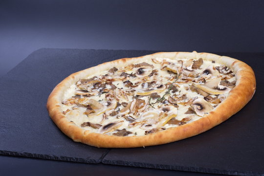 Italian pizza with mushrooms and white sauce lies on a black stone