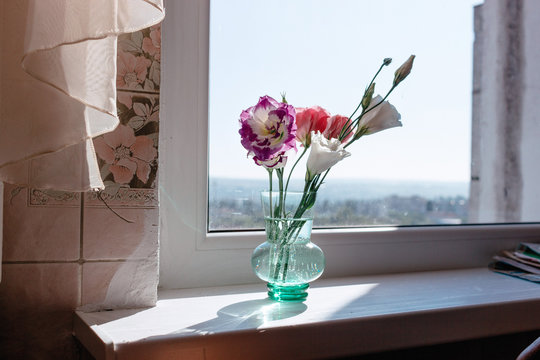 Bouquet of flowers in a glass vase on wooden white table