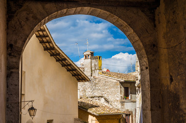A glimpse of Spoleto characteristic roofs through 'Porta Fuga' ancient gate arch