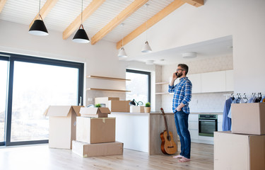 Mature man with boxes moving in new house, using smartphone.
