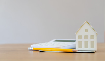 close up front view group of  home model with calculator , yellow pencil, banking account book and calendar on white color background  for money management ,home loan and personal financial concept