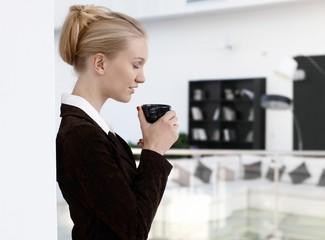 Businesswoman enjoying morning coffee at office