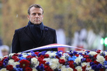 French President Emmanuel Macron stands by a wreath of flowers during a ceremony at the Arc de Triomphe