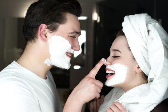 funny couple handsome man applying jokingly foam on beautiful woman's nose having fun both with shaving foam on their faces in bathroom laughing humor moment