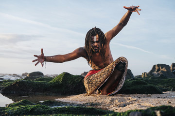 Outdoor emotional scary Fashion Portrait of African man wearing long dreadlocks and fancy makeup white face paint