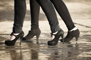 Unrecognizable young women walking in black skinny jeans and high heels across puddles on a sidewalk