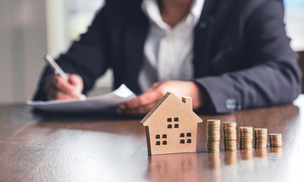Modeling wooden houses and coins and dollars placed on wooden tables,preparation concept for house model purchase and the fastest growing real estate economy,moving home or renting property via agent