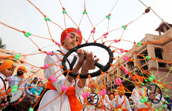A Sikh boy performs 'Gatkha', a traditional form of martial arts during a religious procession on the eve of the 550th birth anniversary of Guru Nanak Dev, the first Sikh Guru and founder of Sikh faith, in Amritsar