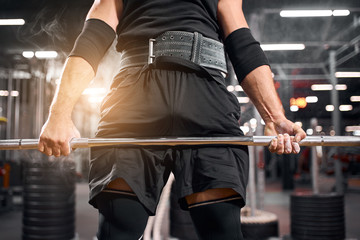 Photo of strong powerful hands of professional powerlifter holding heavy barbell in hands, preparing for workout in brightly lighted gym, shot from below