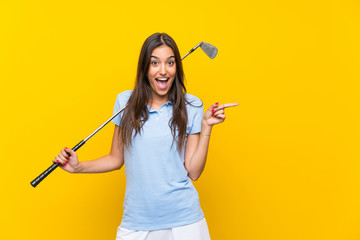 Young golfer woman over isolated yellow wall surprised and pointing finger to the side