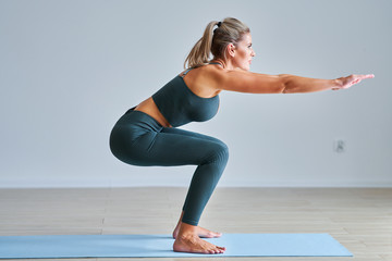 Adult woman practising yoga at home