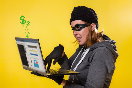 The concept of cybercrime and hacking. Portrait of a woman in a black hat, gloves and mask holding a laptop and engaged in hacking. Yellow background and dollar icons