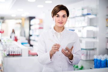 female pharmacist checking assortment of drugs in pharmacy