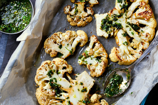Cauliflower steaks with a cilantro lime chimichurri sauce.Top view on a baking paper close-up.Healthy eating,plant based meat substitute concept.Vegetarian organic food.Horizontal orientation