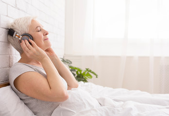 Tranquil senior lady listening to audiobook in bed