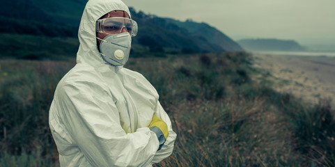 Man in bacteriological protective suit watching to the sea