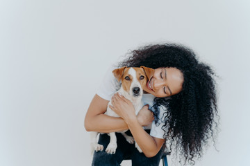 Image of playful pretty woman with Afro hairstyle, smiles gladfully, holds domestic animal, carries dog to veterian, isolated over white background. Glad lady petts jack russell terrier at home.