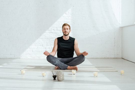 handsome young man practicing yoga in half lotus pose near decorative buddha head, aromatic sticks and candles