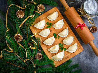Christmas dumplings with decoration on a wooden board. Top view.