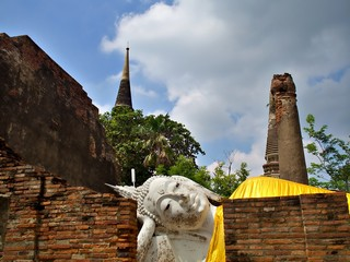 The landscape shot of the ruin of Wat Yai Chaimongkol temple with ancient buddha and stupa in Ayutthaya, Thailand