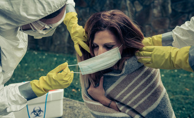 Man and woman in bacteriological protective putting a mask on sick woman