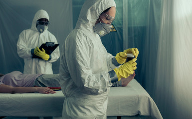 Doctors with bacteriological protection suits preparing medication for sick woman