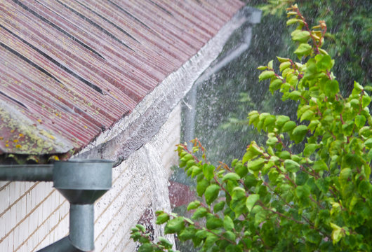 Closeup of leaking rain gutter overflowing with water during the rain
